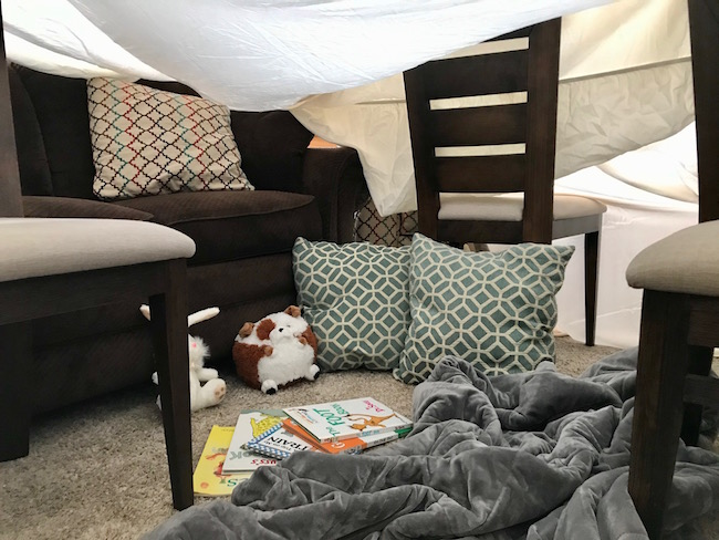 picture of inside of sheet fort with stuffed animals, pillows, blanket and books inside