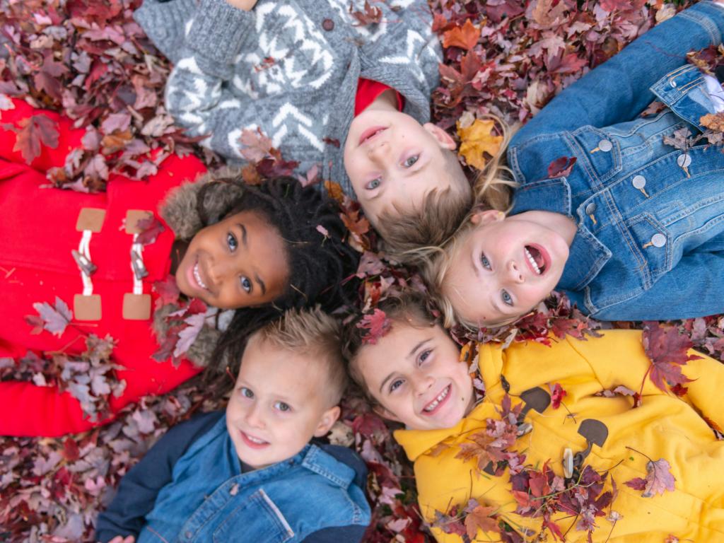 kids lying in fall leaves